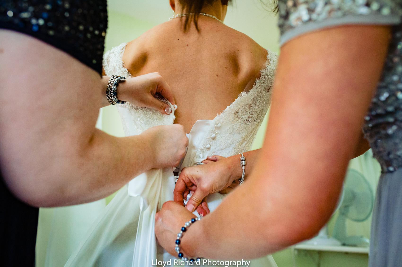 brides dress being done up at Pitt Hall Barn