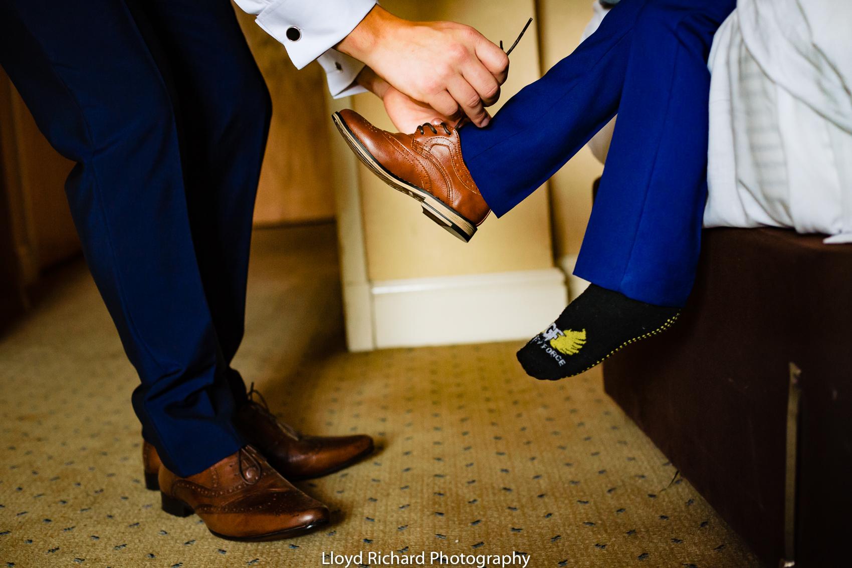 groom tying shoe at Pitt Hall Barn