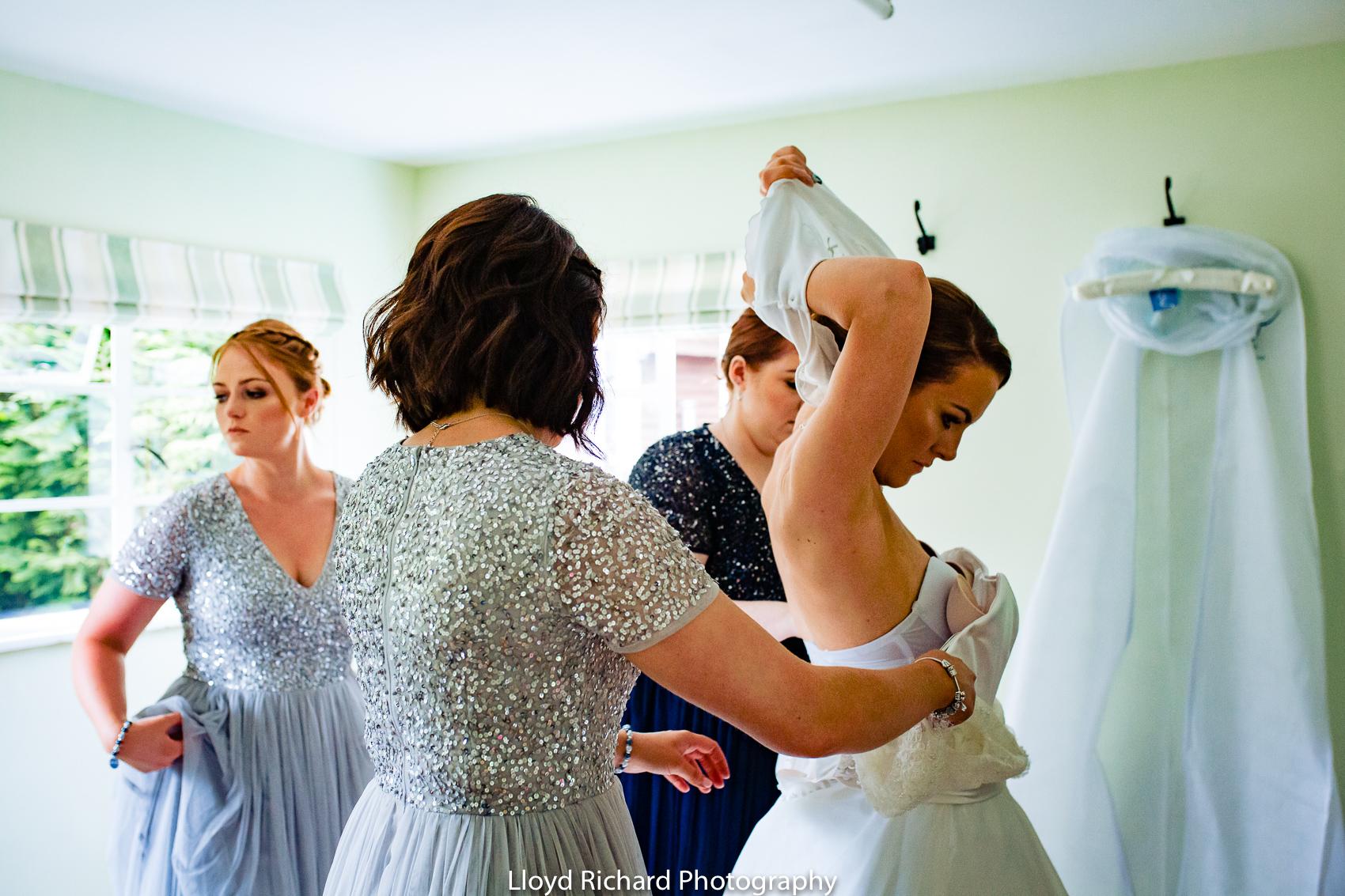 bride getting wedding dress on at Pitt Hall Barn