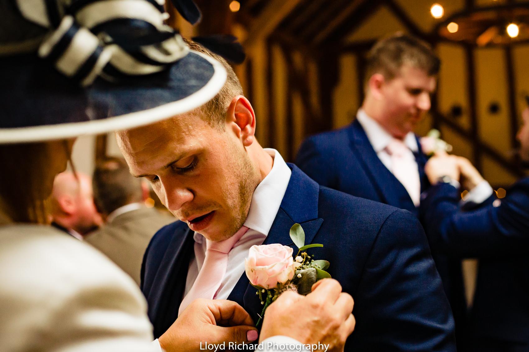 groom putting flower on at Pitt Hall Barn