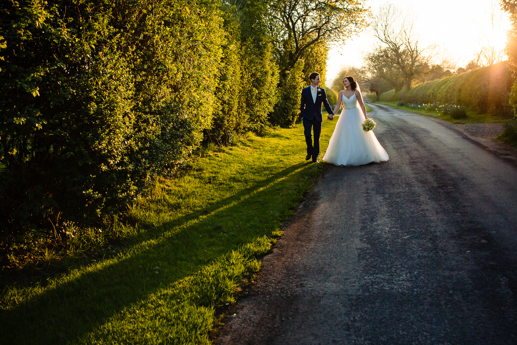 Bride and Groom walking the long private drive at Clock Barn
