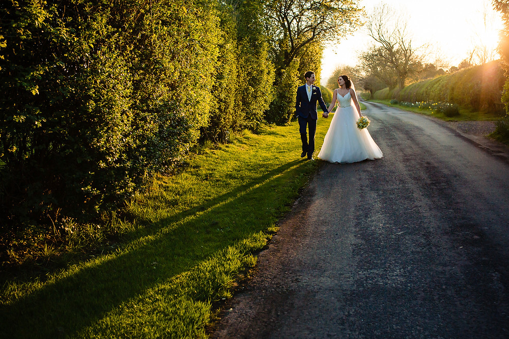 Bride and groom walking down the long private driveway at Clock Barn