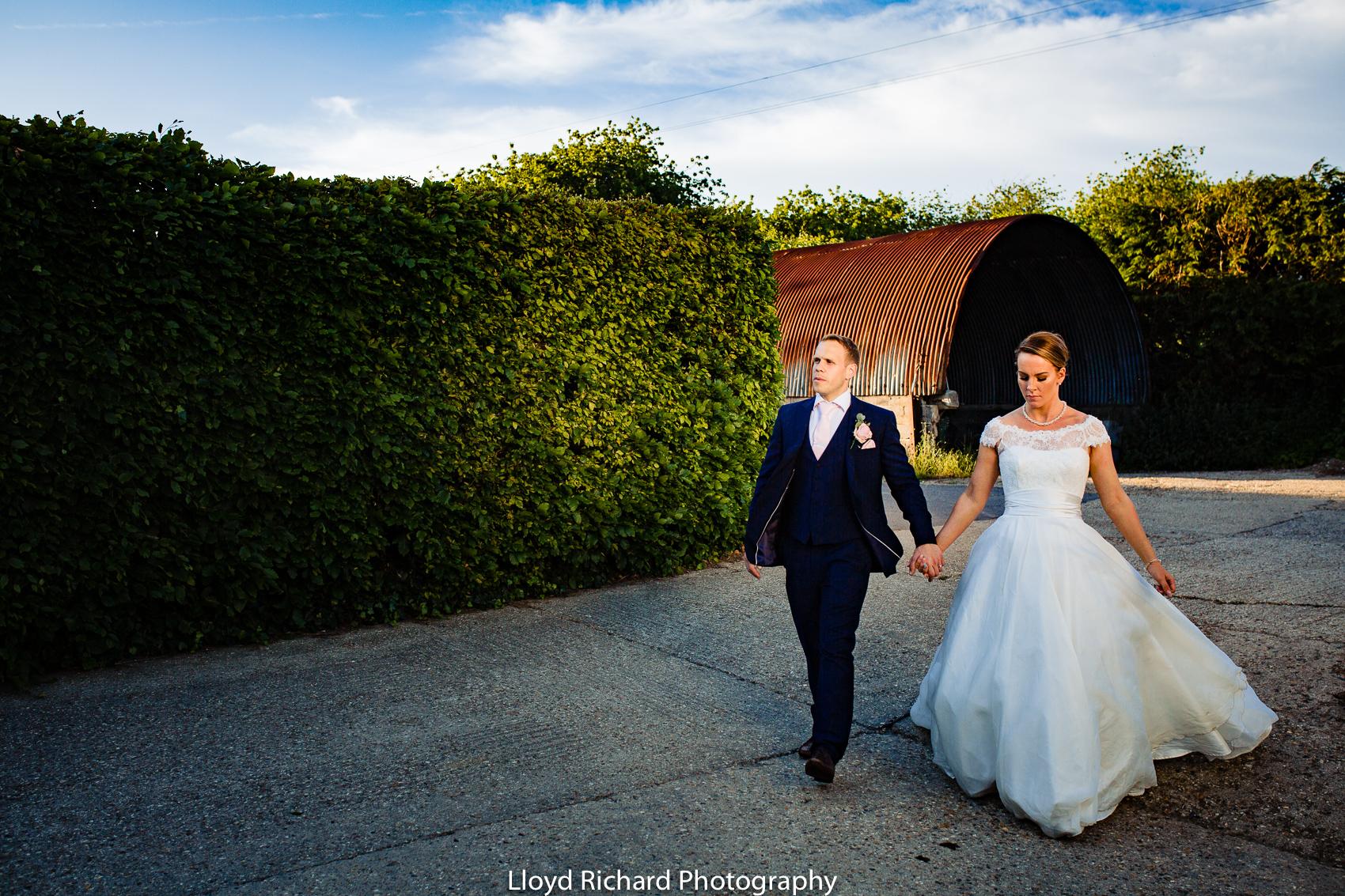 bride and groom walking through Pitt Hall Barn