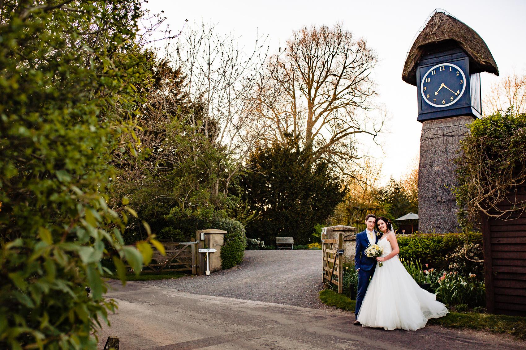 Bride and Groom Outside Clock Barn