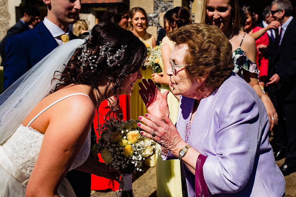 Grandmother photographed greeting bride after church ceremony