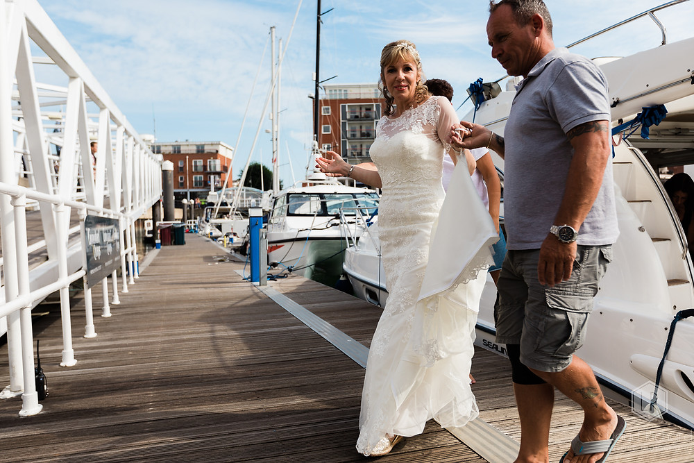 bride stepping onto the jetty