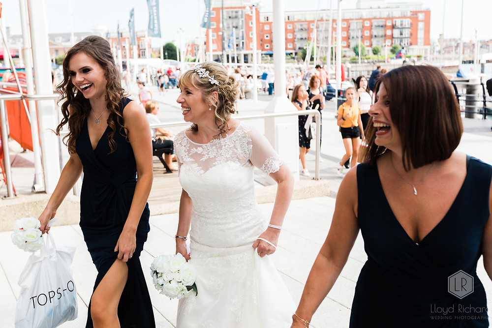 bride and bridesmaids laughing before wedding at spinnaker