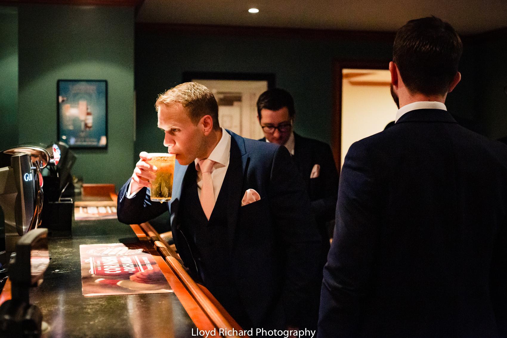 Groom having a drink at Pitt Hall Barn