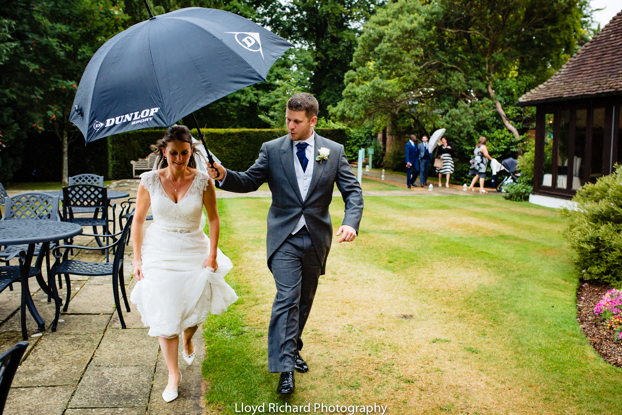 bride and groom walking with umbrella at De Vere New Place Shirrell Heath