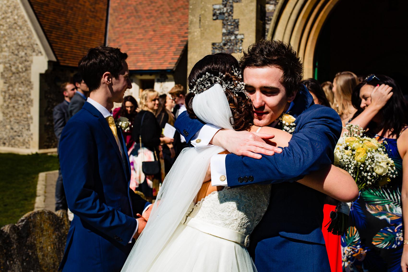bride hugging at St Leonard's Church Sherfield on Loddon