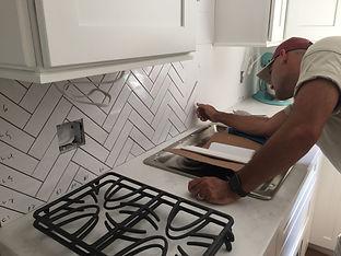 herringbone subway tile being applied