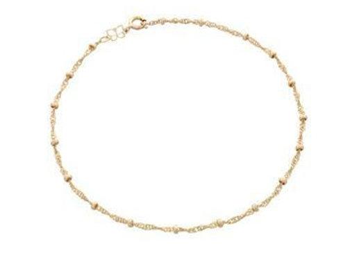 Tornozeleira formada por fio cingapura com bolinhas.