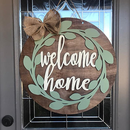 Wooden Doorhanger Farmhouse themed. Says Welcome Home with green ivy around the words.