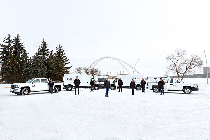 Residential Maintenance Services team standing in front of their vehicle fleet by the Walterdale Bridge in downtown Edmonton