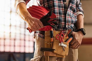 Closeup of man in plaid shirt wearing tool belt