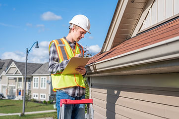Man in safety vest and hardhat inspects roofing