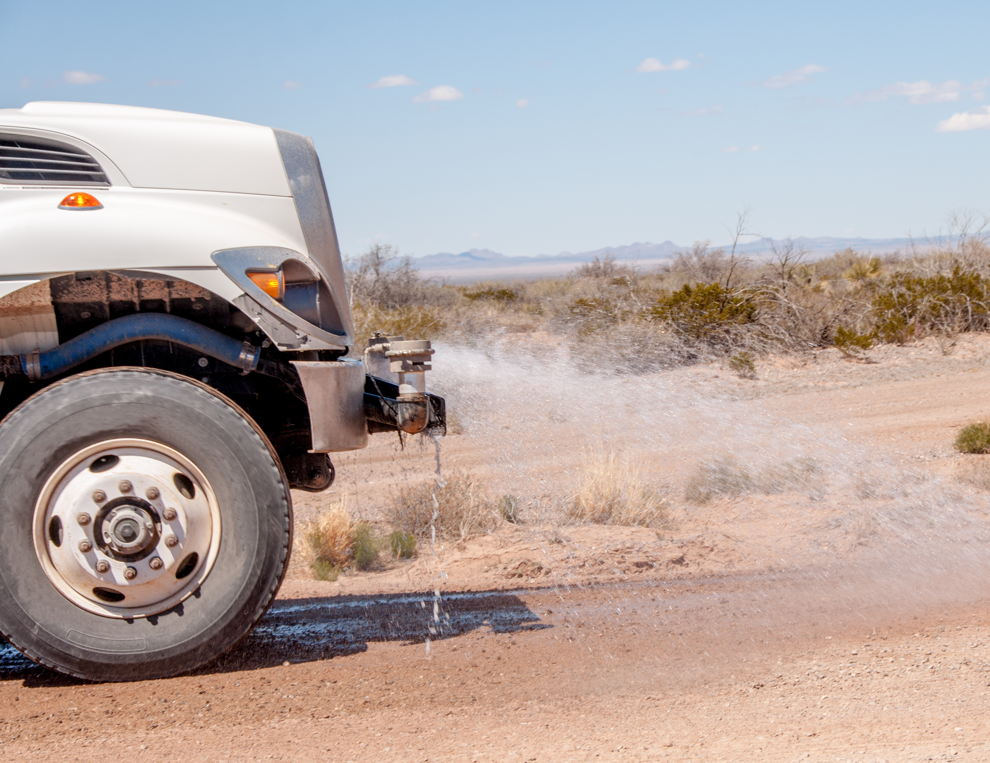 Water-Truck-Controls-Dust-on-Dirt-Road-528965068_3359x2590