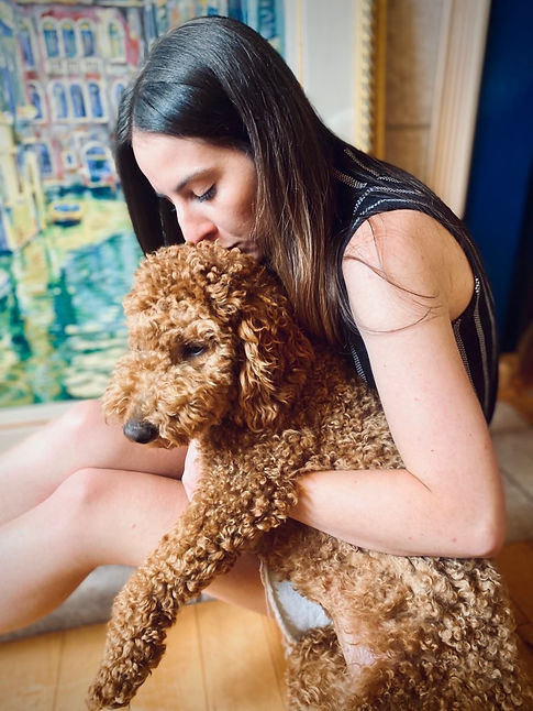 Holding a dog in front of a painting