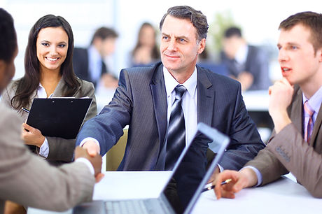 Group in suits shaking hands