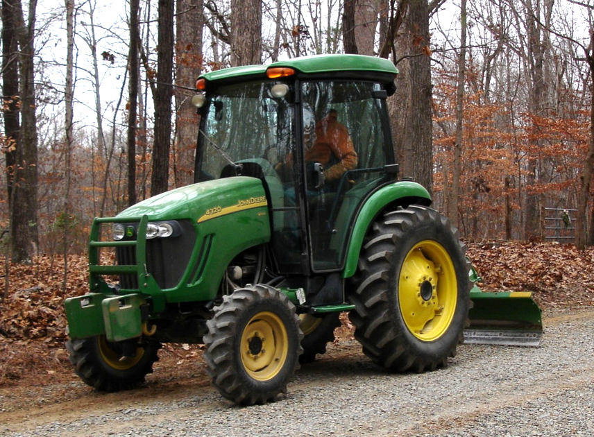 Tractor with motor grader blade