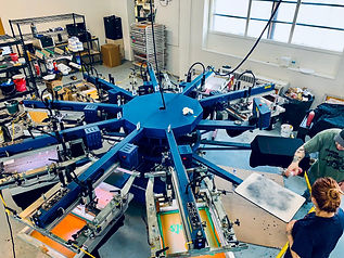 We Make T-Shirts in Racine. Screen printing shirts on our M&R Diamondback E automatic press.