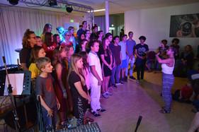 Shelby dirigeert een groep jonge zangers en zangeressen tijdens het MG Muziekkamp 2018