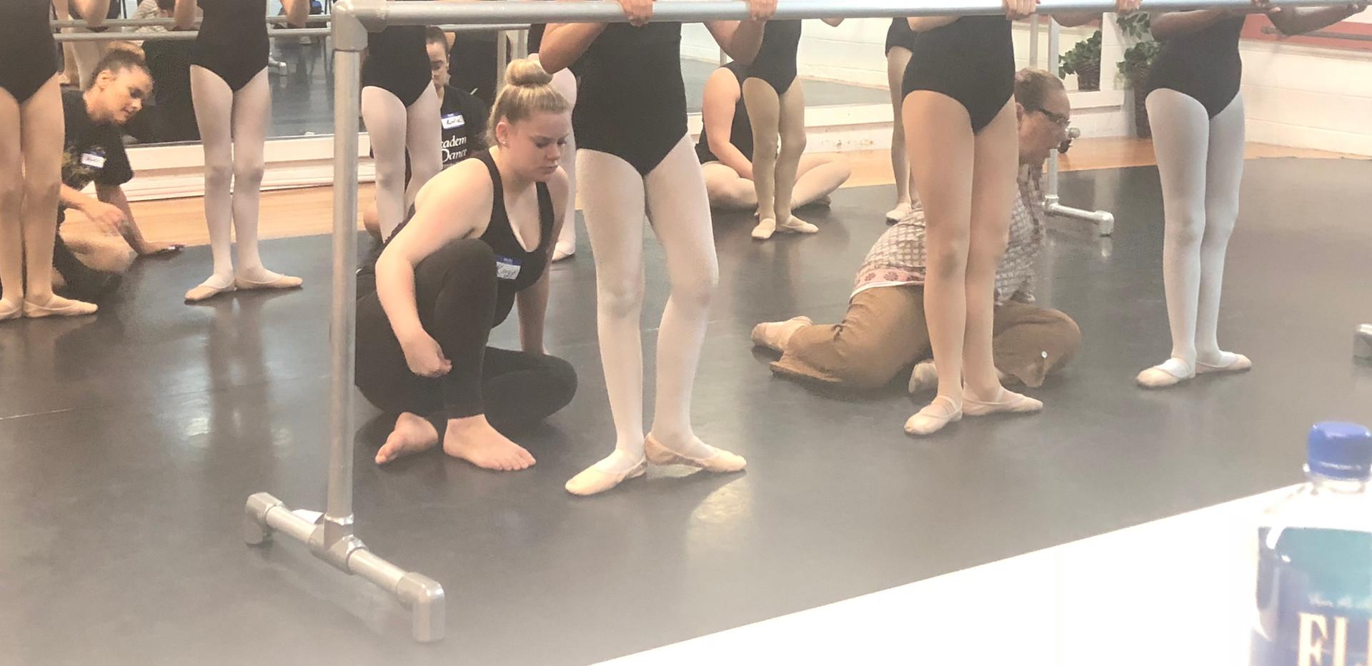 Academy assistant teachers learn proper foot placement during teacher training.