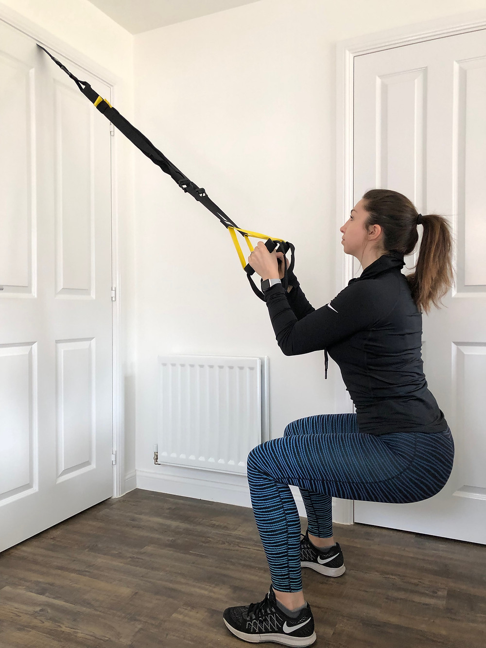 Woman performing a squat using the TRX training at home