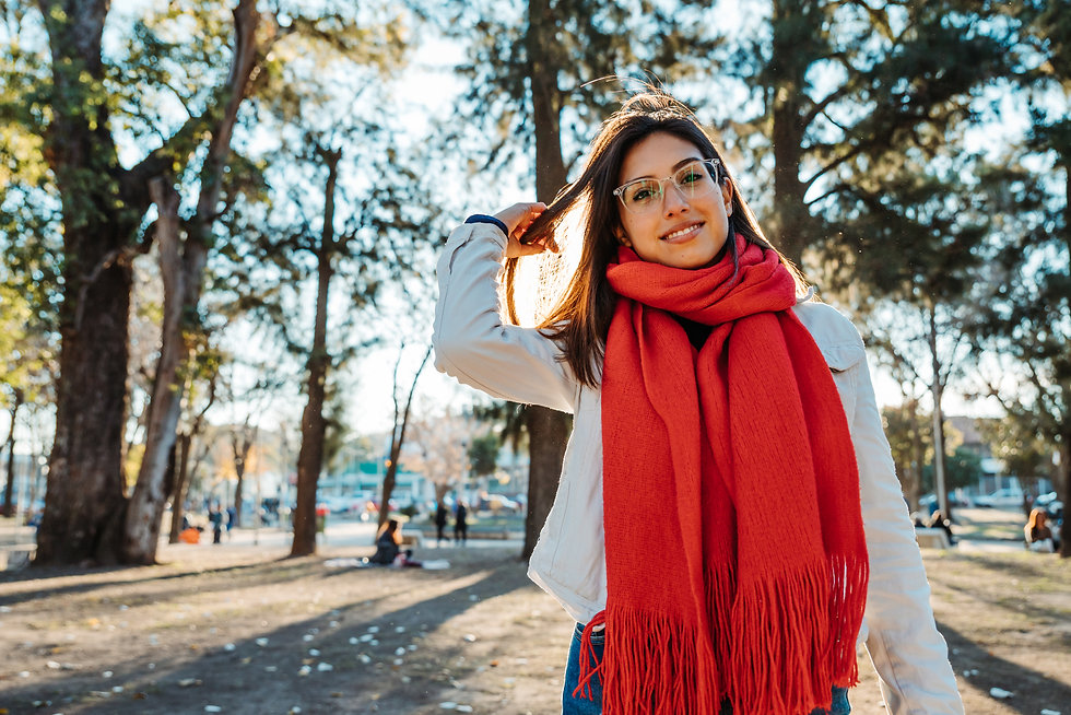 A cheerful Hispanic lady wearing glasses, a scarf with a coat, and jeans in a sunny park.j