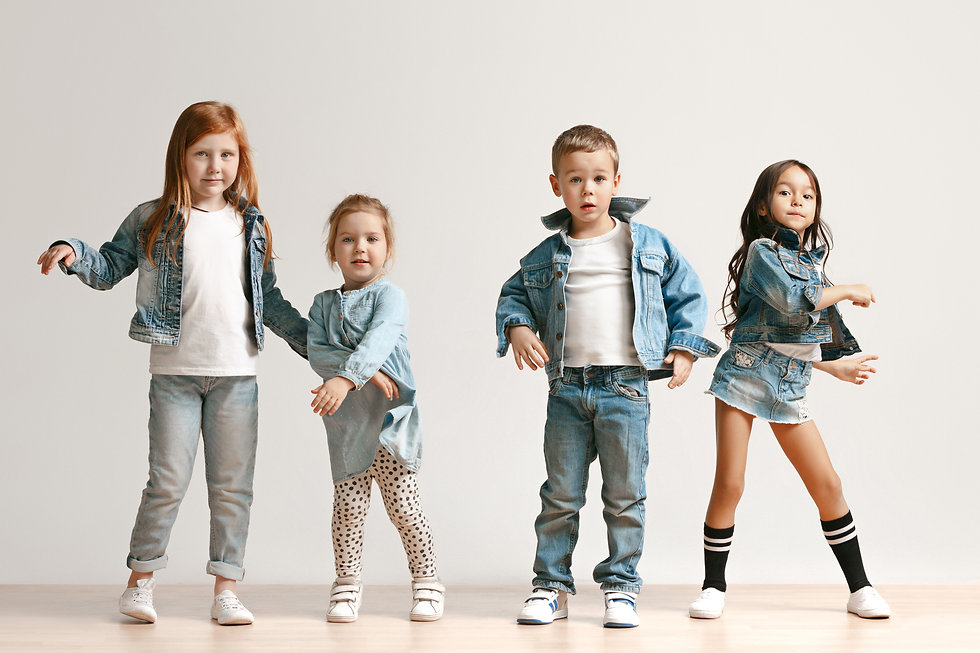 The portrait of cute little kids boy and girls in stylish jeans clothes looking at camera