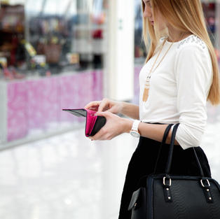 Young stylish woman in cute trendy outfit with leather handbag looking into purse. Close-u