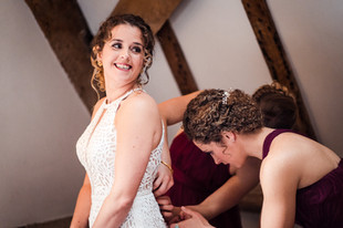Bridesmaids helping the bride into her dress