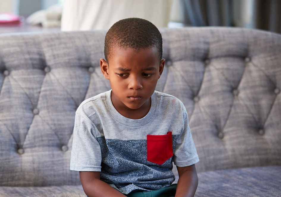 Sad young boy sitting on couch