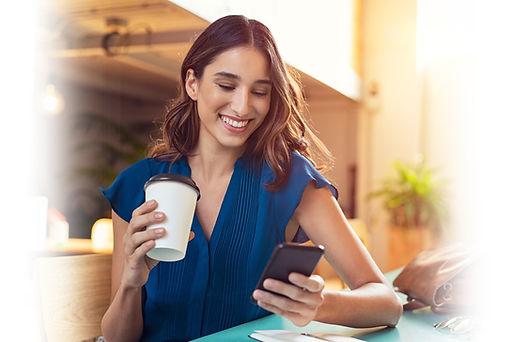 female_holding_coffee_phone_blurred.jpg