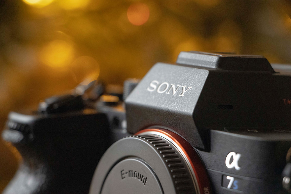 Close up of camera with gold bokeh background