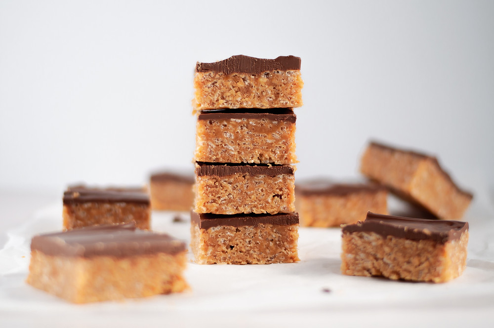 Stack of scotcheroo bars, surrounded by additional scotcheroo bar squares