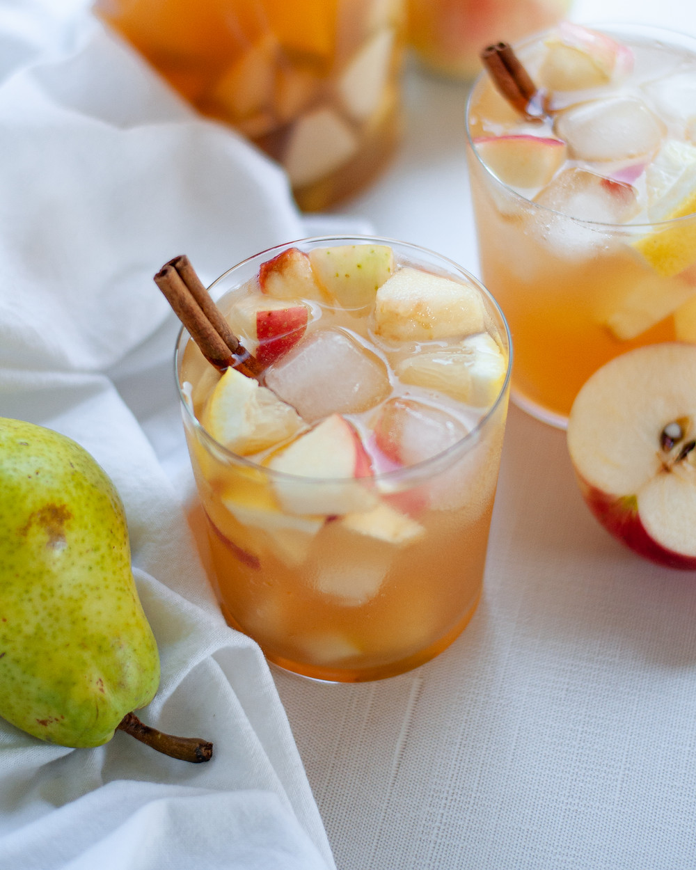A glass filled with fall white wine sangria and garnished with a cinnamon stick. The glass is surrounded by pears and apples and a white napkin.