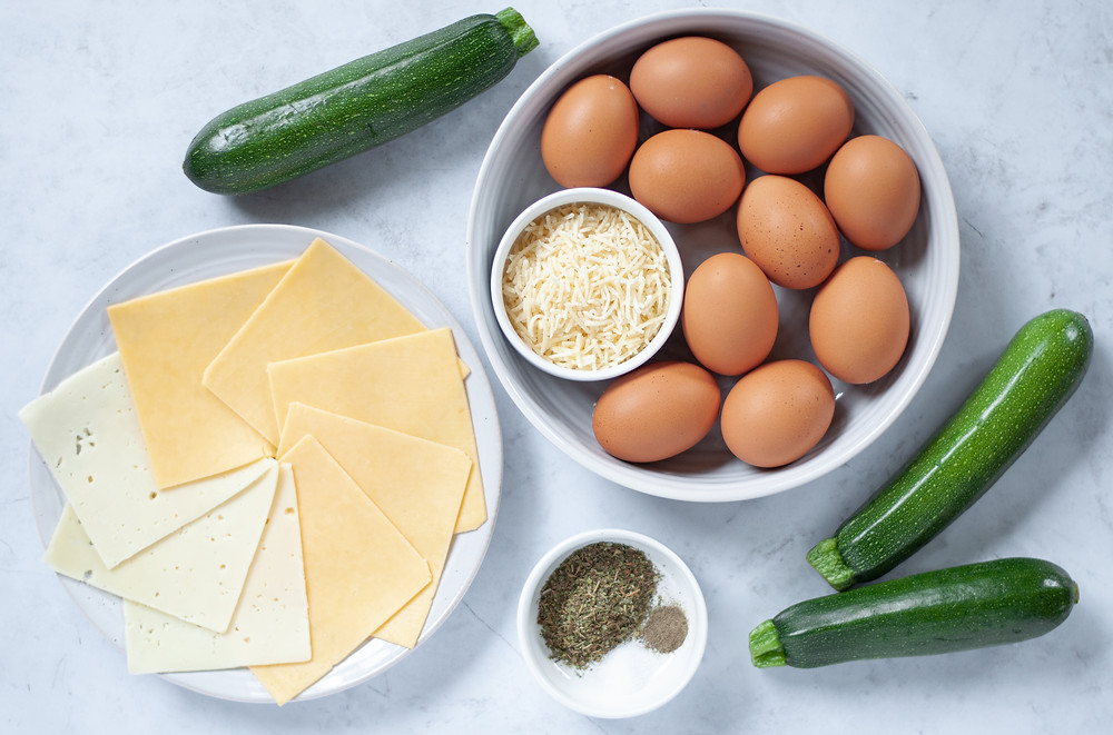 Ingredient shot for this zucchini egg casserole recipe. Shows slices of swiss, gouda, shredded parmesan, zucchinis, eggs, and spices.