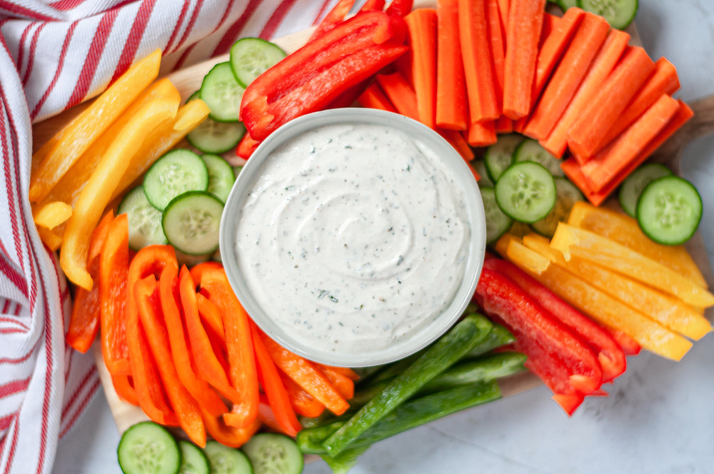 Top down view of a veggie tray with a serving bowl of ranch vegetable dip in the center.