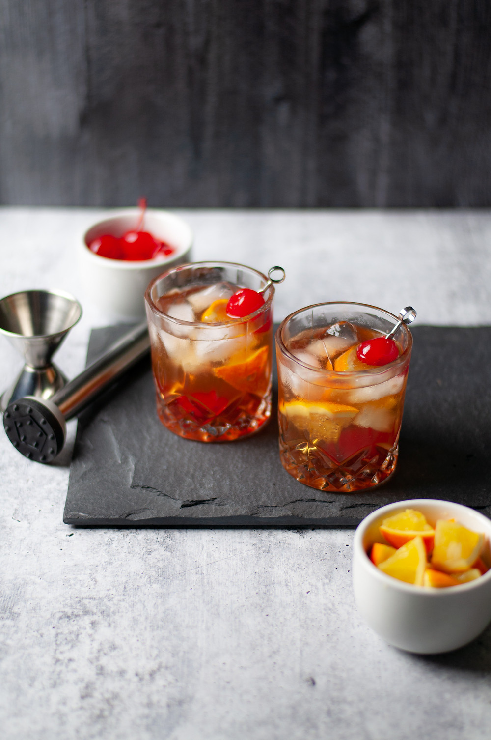 Two rocks glasses filled with this classic Wisconsin Brandy Old Fashioned Recipe and garnished with orange slices and a cherry, next to a muddler and jigger
