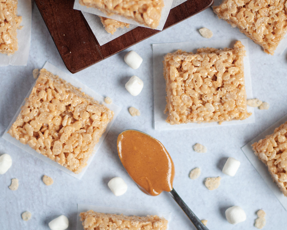top down view of several peanut butter rice krispy squares. surrounded by mini marshmallows, rice krispie cereal, and a spoon full of creamy peanut butter