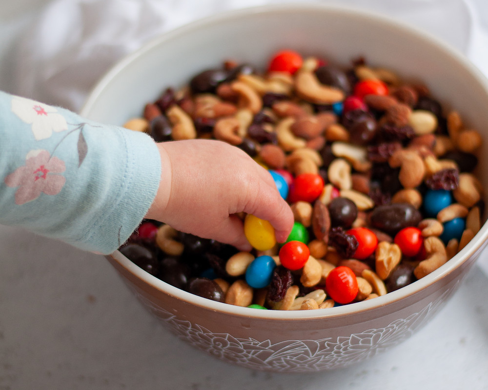 A child's hand reaching into a bowl of this homemade trail mix recipe.