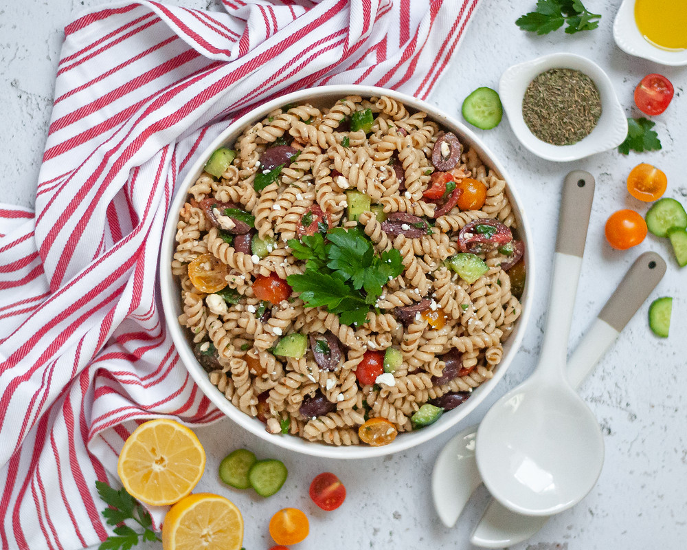 Top down view of a serving bowl filled with this vegetarian pasta salad surrounded by ingredients, serving spoons, and a striped napkin.