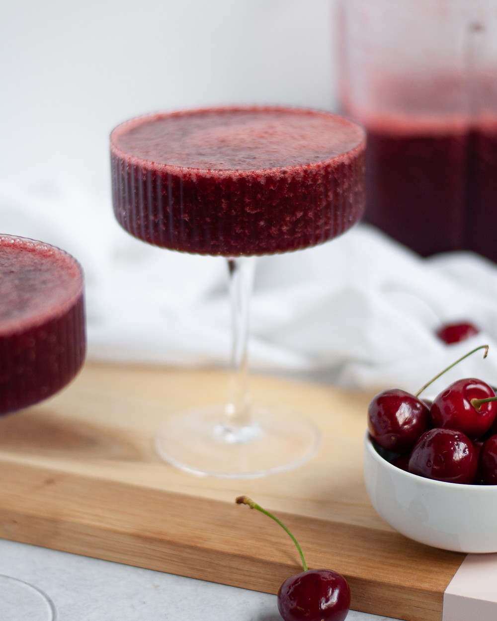 Straight on view of a coupe glass filled with cherry wine slushies. Another glass filled is in the foreground peaking into the frame, there is a bowl of cherries, and the pitcher of frose is in the background.