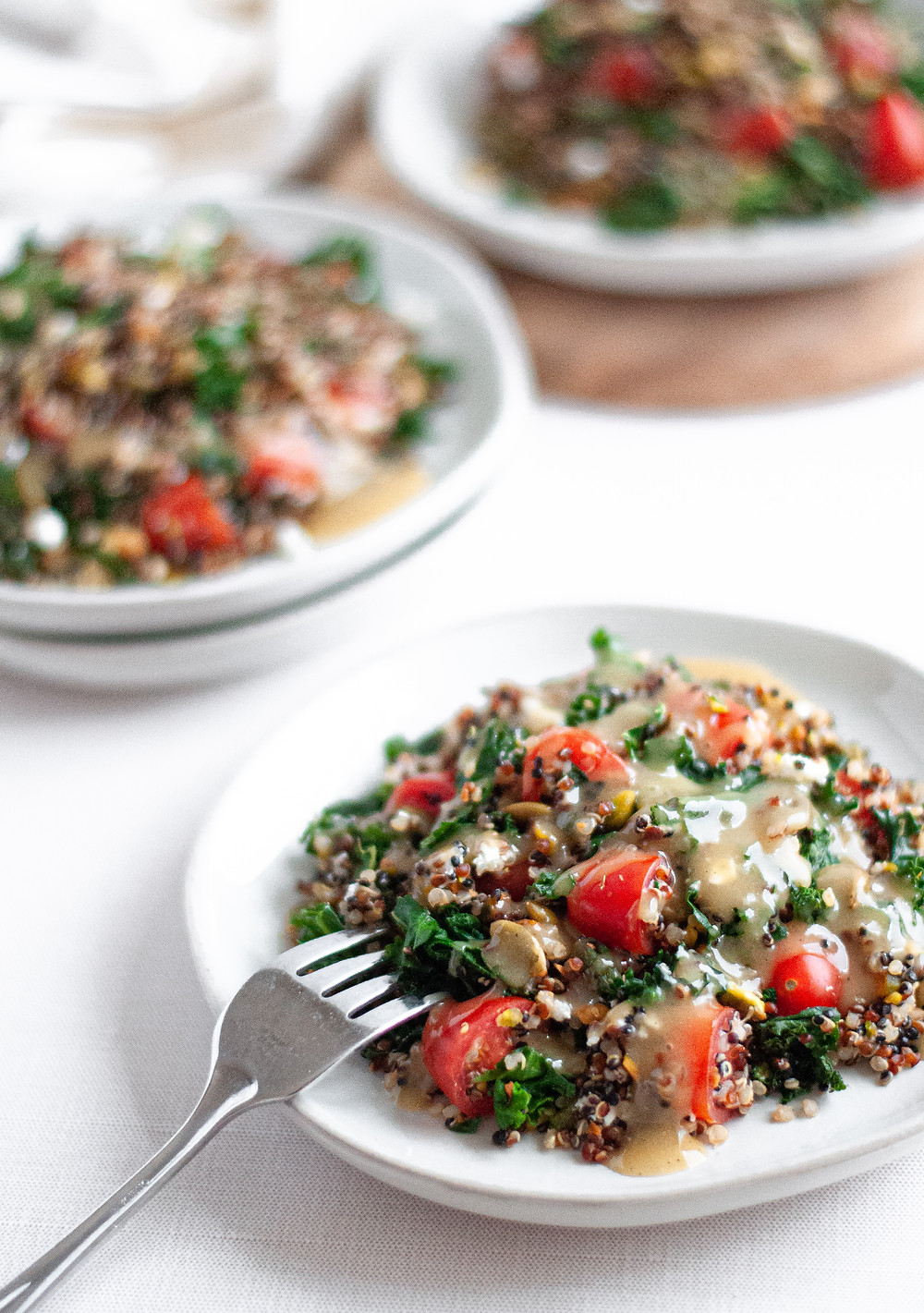 Three plates of kale and quinoa salad, topped with homemade maple tahini dressing