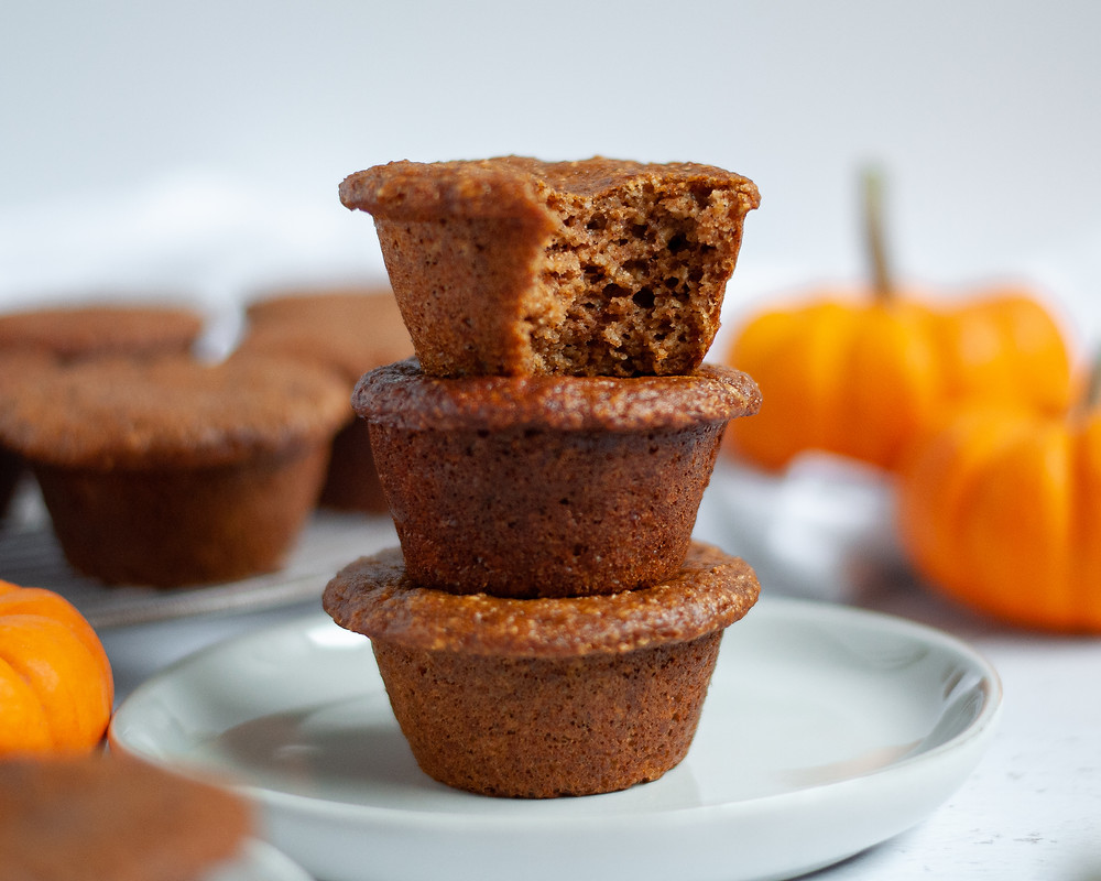 Stack of 3 protein pumpkin muffins on a plate. The top muffin has a bite taken out of it. There are more gluten free pumpkin muffins in the background as well as mini pumpkins.