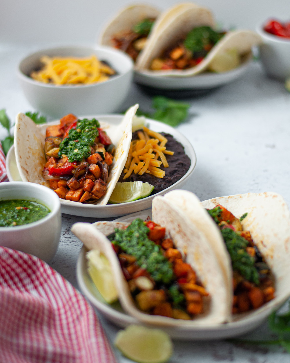 Three plates of this vegetarian taco recipe served up and ready to eat. Each vegetable taco is covered in homemade chimichurri sauce, and there is a side of refried beans with cheese