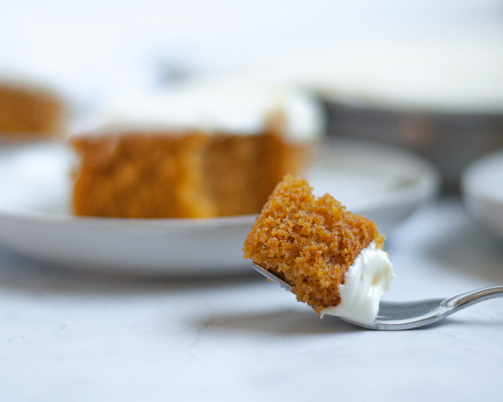 Close up of a fork with a bite of pumpkin bar on it. In the background you can see a plate with a pumpkin square on it