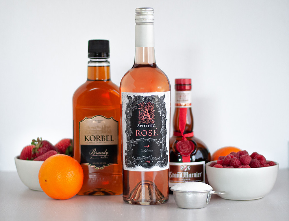 Ingredients for rosé sangria, including a bottles of rosé wine, Korbel brandy, and Grand Marnier. A 1/4 cup measure filled with granulated sugar, 2 oranges, and bowls of strawberries and raspberries.