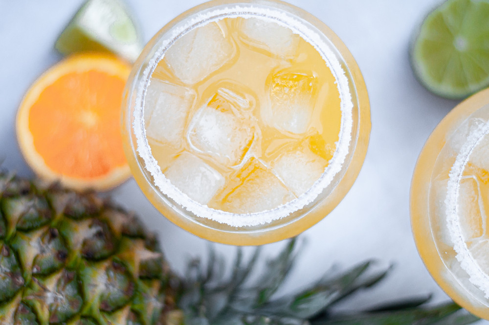 Top down view of a glass of this pineapple cocktail, with fresh oranges, limes, and a pineapple surrounding it.